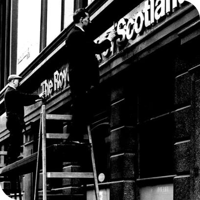 man putting up royal bank of Scotland sign